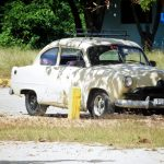 a car parked by a litter bin and a tree in playa ancón close to Trinidad in Cuba