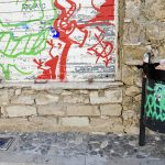 a litter bin with a green tag in a street with graffitis in Limassol Cyprus
