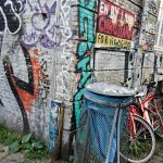 blue litter bin in Christiana Denmark in Copenhagen by graffitis and red bicycles