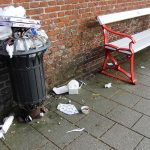 a very full bin by a bench in Ribe Denmark after a town festival