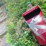 a red litter bin in a park in Luxembourg city