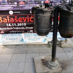 double black litter bins in the street of Skopje Macedonia in front of an advertisement for a concert of Balasevic