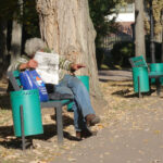 man reading the newspaper on a bench by matching green bins in Chisinau, Moldova