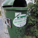 a green trash can tied up to a tree in Bucarest Romania