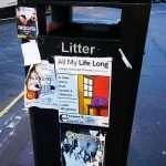 a litter bin in a street of Edinburgh Scotland United Kingdom full of advertisements