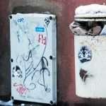 a full litter bin in a street on a wall in Talinn Estonia