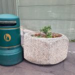 a green litter bin by a pot with a plant on the parking lot of the supermarket Auchan in Leers France close to the Belgium border