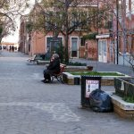 a black litter bin in a street by benches in Murano in Italy