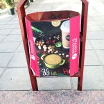a litter bin in a street of Chisinau Moldova with coffee advertisement on it