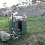 a green litter bin in side the Amphitheatre of Durrës in Albania