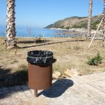 a brown litter bin in the beach town of Jale in Albania
