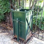 a green litter bin in a park in Tirana Albania