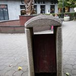 a litter bin in Pristina Kosovo in front of a statue of Mother Theresa