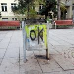 a litter bin in the main street of Pristina, Nena Tereza street in Kosovo with OK tagged on it with benches in the background