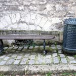 a litter bin by a bench in a street of medieval town PROVINS in France World Heritage site UNESCO
