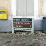 a litter bin by signs and a post box in Provins France