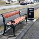 a black litter bin by a bench in Reykavik Iceland