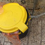 a yellow litter bin in a street of Jerusalem tied up to the wall