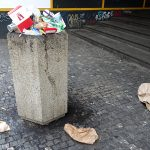 a very full litter bin in a street in Prague close to junk food places in the Czech Republic