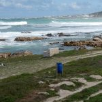 a blue litter bin by the side of the sea arriving in cape agulhas where the atlantic ocean meets the indian ocean at the southermost tip of Africa