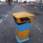 a yellow and blue street litter bin in the desert town of Swakopmund in Namibia